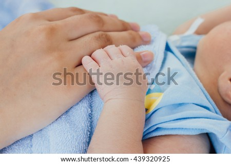 newborn baby hand on mother hand with blue blanket : mother day and people concept - stock photo