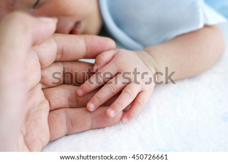 Newborn baby hand with father hand