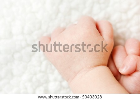 newborn baby hands on a blanket with copy space - stock photo