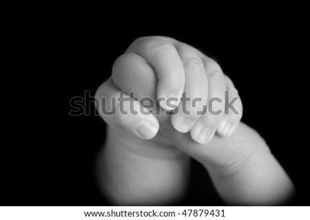 Newborn baby holding mother's finger - stock photo