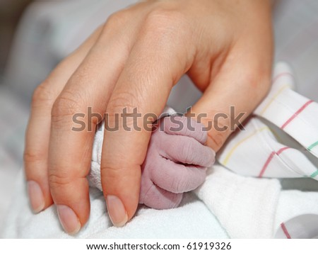 Newborn baby holds mothers hand - stock photo
