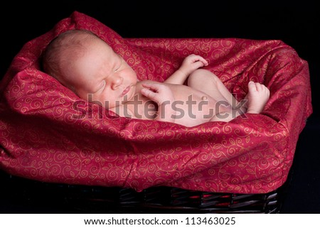 Newborn baby in a basket - stock photo