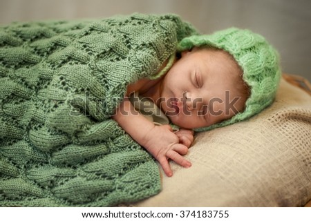 newborn baby in a green knitted hat sleeping