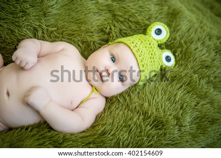 newborn baby in a hat frog lying on stomach