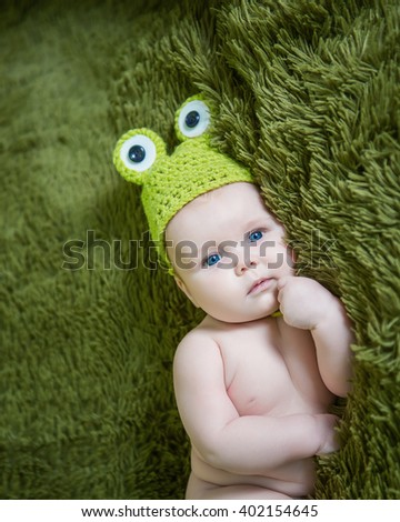newborn baby in a hat frog lying on stomach - stock photo
