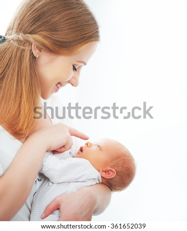 newborn baby in a tender embrace of mother at the window - stock photo