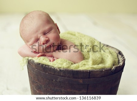 Newborn baby in antique planter bucket. - stock photo