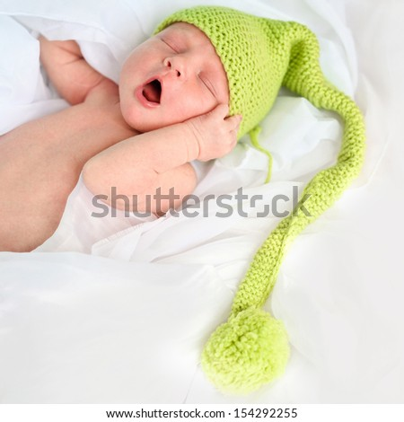 newborn baby in blue hat - stock photo
