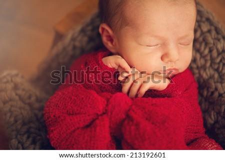 Newborn Baby in cocoon - close portrait of child - stock photo
