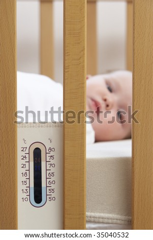 Newborn Baby In Cot With Thermometer - stock photo