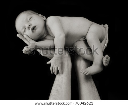 Newborn baby in hands, shallow depth of field, low key lighting