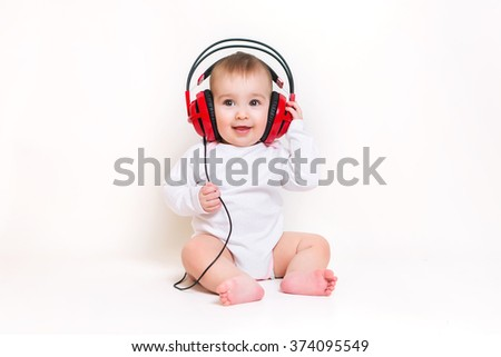 Newborn baby in headphones listening to music - stock photo