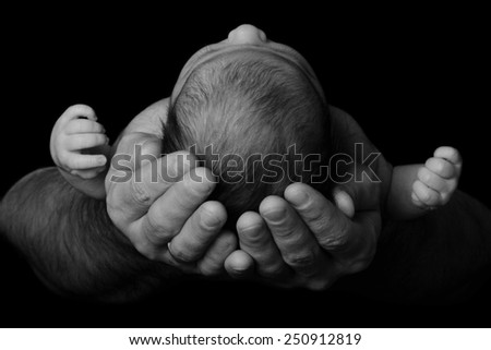 Newborn baby in the arms of his father, close-up. black and white photography - stock photo