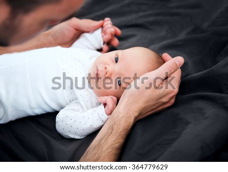 Newborn baby in the hands of his father - stock photo