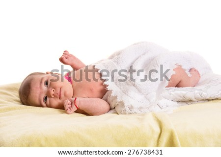 Newborn baby in white soft blanket laying on back