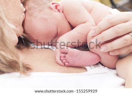 Newborn baby is asleep on mother's chest - stock photo