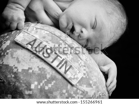 Newborn baby is laying on army helmet