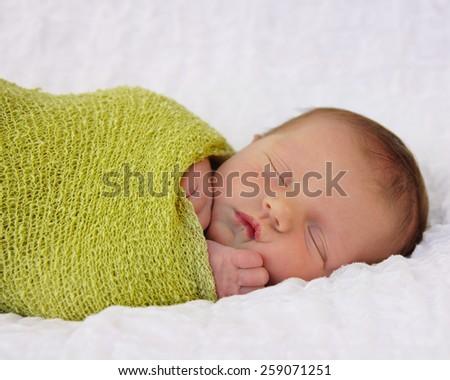 Newborn baby lay sleeping - stock photo