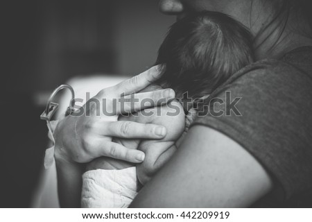 Newborn baby laying on moms chest in hospital - stock photo