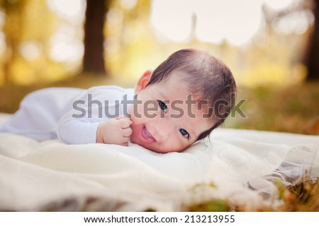 Newborn baby laying on the grass in the autumn park - stock photo
