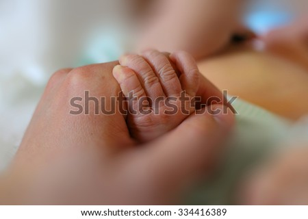 Newborn baby little hand hold by adult man hand of his father