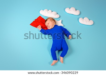 Newborn baby. Little super hero flying through the sky.  - stock photo