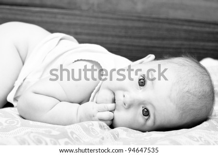newborn baby lying and looking at camera with interest.  Black and white photo - stock photo