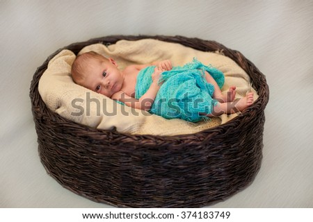 newborn baby lying calm in a basket - stock photo