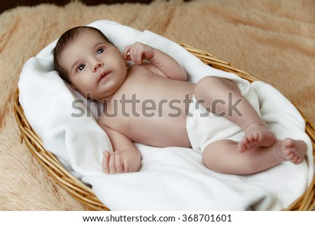 Newborn baby lying in wicker basket