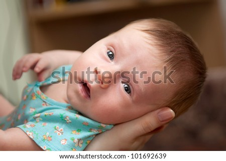 Newborn baby lying on his mother's arms and looking into the camera. Focus on the baby's face - stock photo