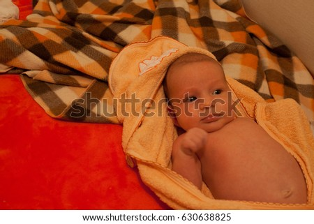 newborn baby lying on the bed