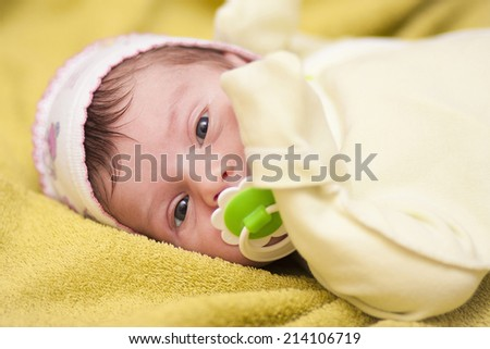 newborn baby lying on the bed with a pacifier - stock photo