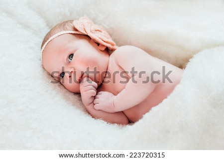 Newborn baby lying on white and soft blanket - stock photo