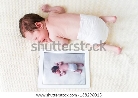 Newborn baby next to her photo on a tablet pc - stock photo