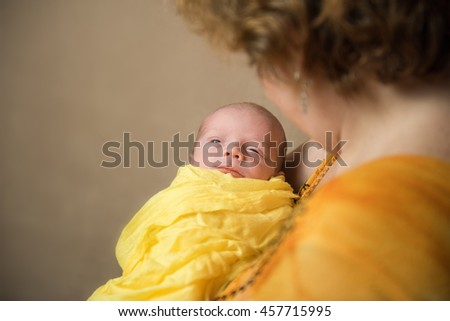 Newborn baby on hands at mum. In yellow clothes - stock photo