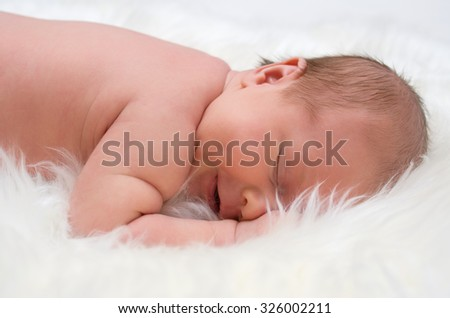 Newborn baby on white furs