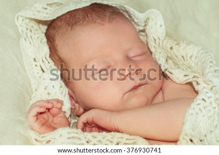 Newborn baby peacefully sleeping.Adorable beautiful newborn baby girl. Maternity and newborn concept. Baby newborn sleeping covered on white woolen blanket. - stock photo