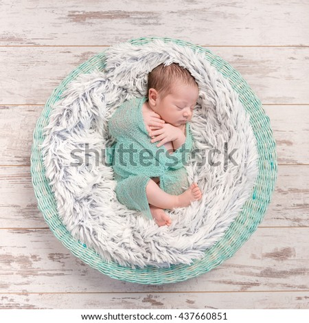 newborn baby peacefully sleeping in round cot with fluffy blanket, top view - stock photo
