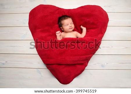 Newborn baby peacefully sleeping on a red blanket in the form of heart  - stock photo