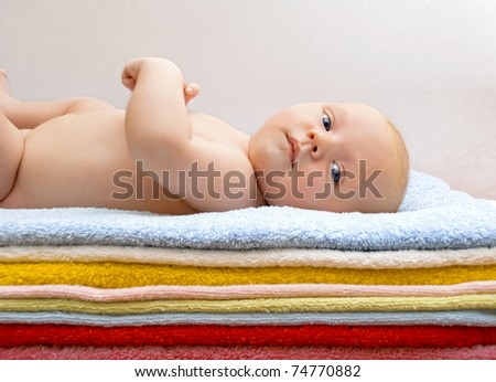 Newborn baby relaxing on the colored towels - stock photo