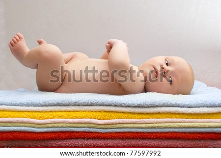 Newborn baby relaxing on the colored towels. - stock photo