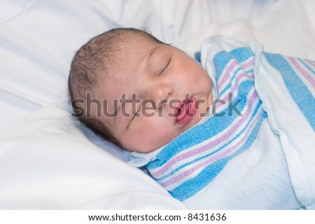 Newborn baby resting with tongue sticking out - stock photo