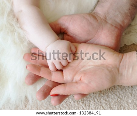 newborn baby's hand lay in the hand of it's mother and father - stock photo