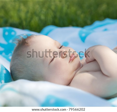 Newborn baby sleep on towel in park - stock photo