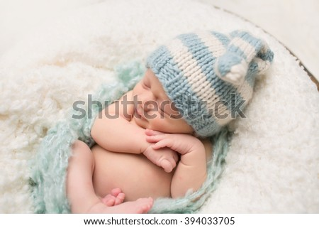 Newborn Baby sleeping, asleep happy and smiling, on a blanket, wearing a knit hat - stock photo