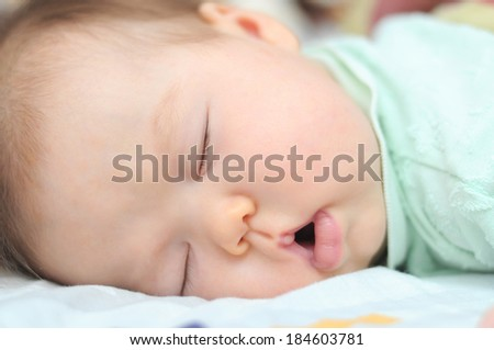 Newborn baby sleeping at night portrait with open mouth, cute and adorable baby face