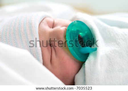 Newborn baby sleeping bundled in blankets with pacifier