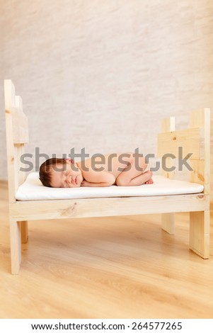 newborn baby sleeping in a baby cot - stock photo