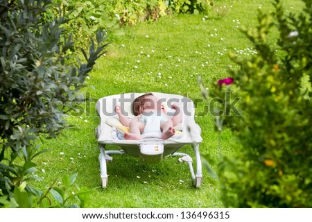 Newborn baby sleeping in a bouncer in the garden - stock photo