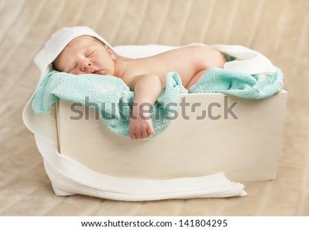 Newborn baby sleeping in a wooden case - stock photo